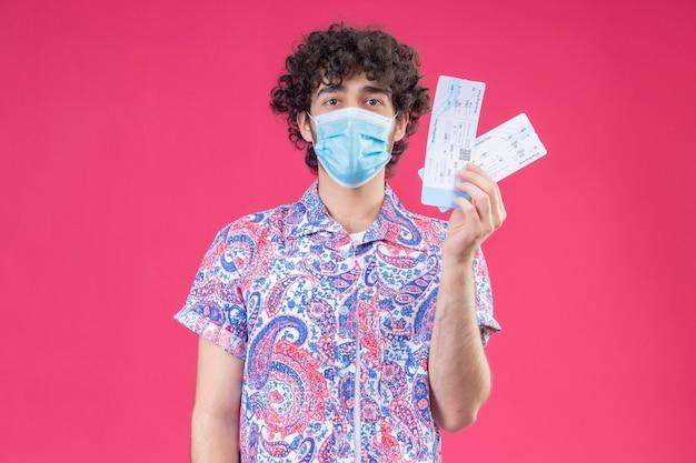 コピースペースと孤立したピンクの壁に飛行機のチケットを保持している医療マスクを身に着けている若いハンサムな巻き毛の旅行者の男