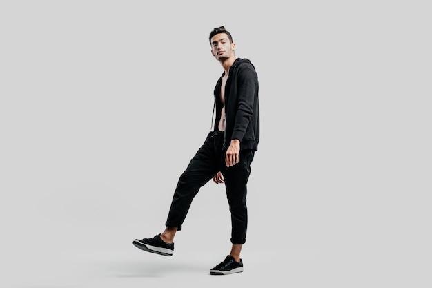 黒のズボンと裸の胴体にスウェットシャツを着た若いハンサムなダンサーは、白い背景の上に立っています