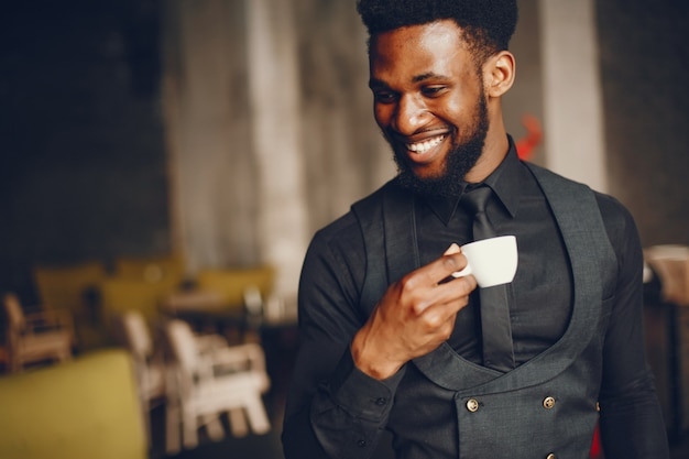 A young and handsome dark-skinned boy in a black suit standing in a cafe