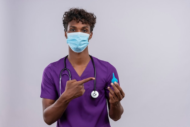 A young handsome dark-skinned doctor with curly hair wearing violet uniform with stethoscope in face mask pointing at an enema with index finger