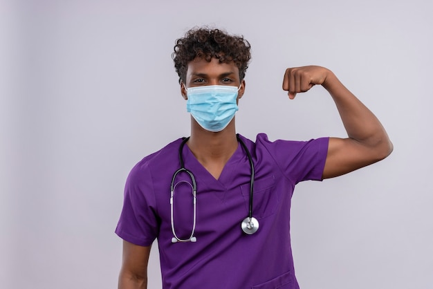 A young handsome dark-skinned doctor with curly hair wearing violet uniform with stethoscope in face mask showing strength gesture