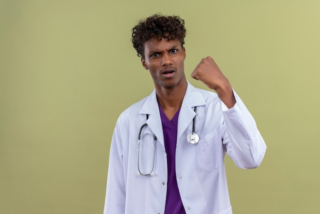 A young handsome dark-skinned doctor with curly hair wearing white coat with stethoscope with aggressive expression showing clenched fist on a green space