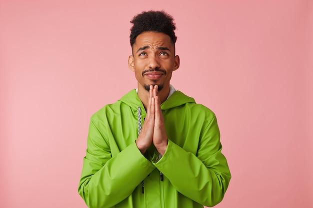緑のレインコートを着た若いハンサムな黒い肌の男は、彼のあごに手をかざし、見上げて、彼が試験で幸運であることを祈り、立っています。