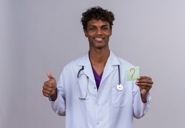 A young handsome dark-skinned male doctor with curly hair wearing white coat with stethoscope showing a paper card with the question mark