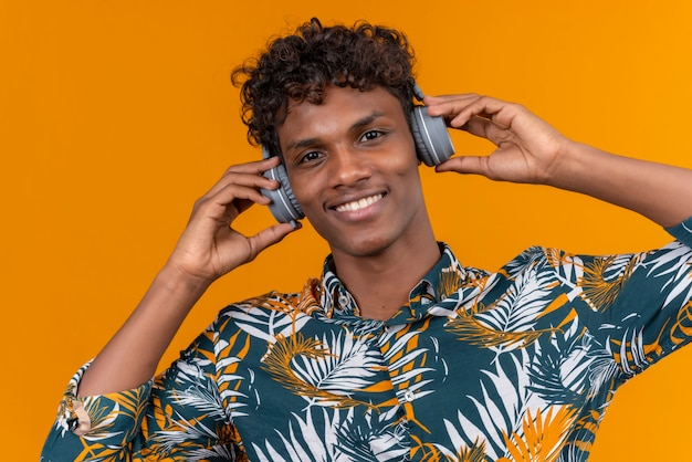 A young handsome dark-skinned man with curly hair in leaves printed shirt in headphones smiling keeping hands on headphones