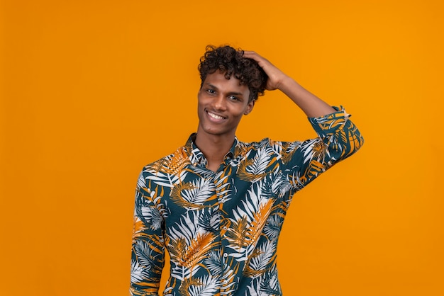 A young handsome dark-skinned man with curly hair in leaves printed shirt keeping hand on head