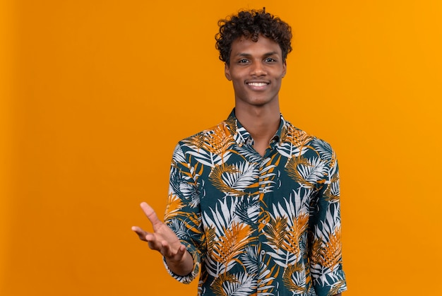 A young handsome dark-skinned man with curly hair in leaves printed shirt smiling and raising hand