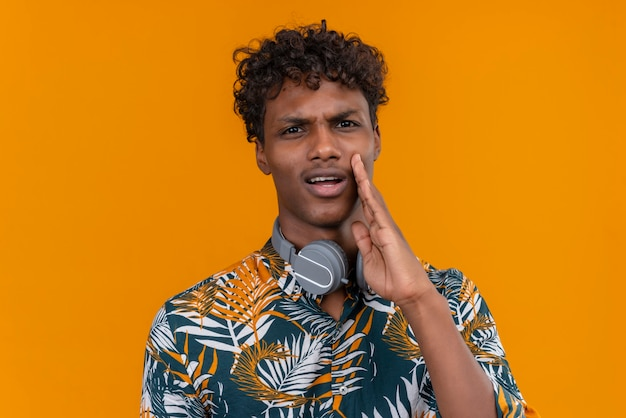 A young handsome dark-skinned man with curly hair in leaves printed shirt with aggressive face calling someone holding hand on face