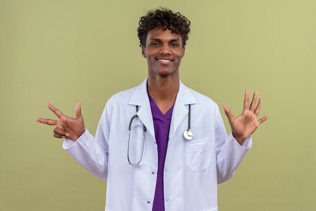 A young handsome dark-skinned man with curly hair wearing white coat with stethoscope showing number eight on a green space