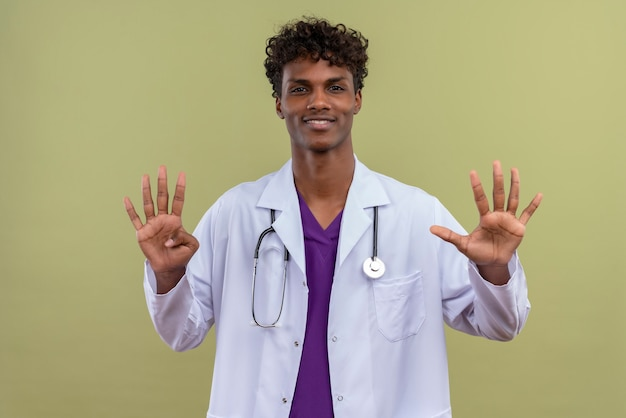 A young handsome dark-skinned man with curly hair wearing white coat with stethoscope showing number nine on a green space
