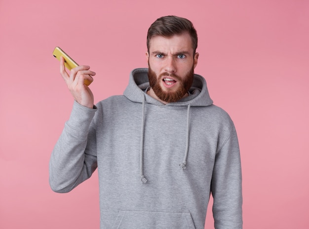 Giovane uomo barbuto rosso bello stordito in felpa con cappuccio grigia, sembra scontento, parla al telefono con la sua ragazza e ha perso la connessione al telefono, si trova su sfondo rosa.