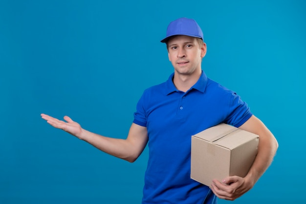 Young handsome delivery man in blue uniform and cap holding box package presenting with arm of his hand copy space smiling standing over blue wall