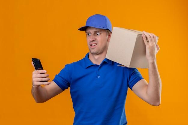 Giovane uomo di consegna bello in uniforme blu e pacchetto della scatola della tenuta del cappuccio sulla spalla
