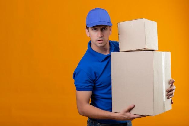 Giovane uomo di consegna bello in uniforme blu e cappuccio che tiene scatole di cartone stanche e oberate di lavoro con l'espressione triste sul viso in piedi sopra la parete arancione