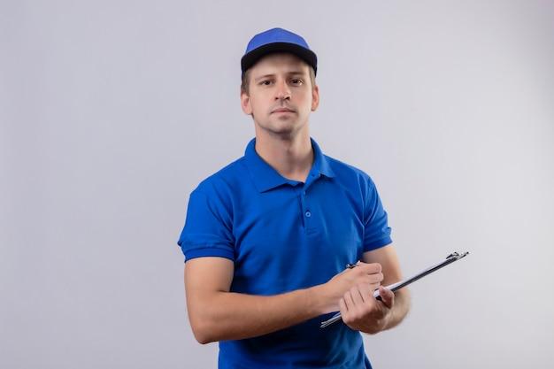 Giovane uomo di consegna bello in uniforme blu e cappuccio che tiene appunti con la penna che sembra fiducioso in piedi sopra il muro bianco