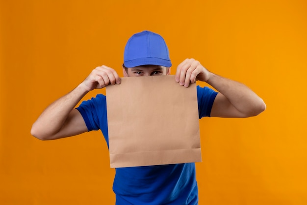 Young handsome delivery man in blue uniform and cap holding paper package