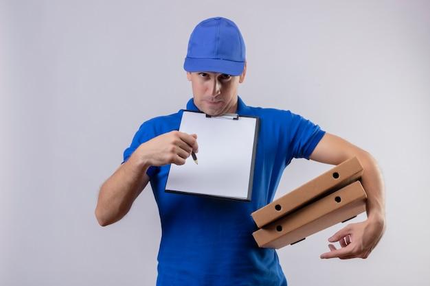 Giovane uomo di consegna bello in uniforme blu e cappuccio che tiene scatole per pizza e appunti con spazi vuoti che chiedono la firma in piedi sopra il muro bianco