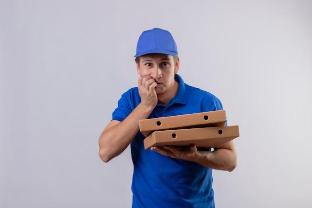 Giovane uomo di consegna bello in uniforme blu e cappuccio che tiene le scatole della pizza stressato e nervoso che si morde le unghie in piedi sul muro bianco