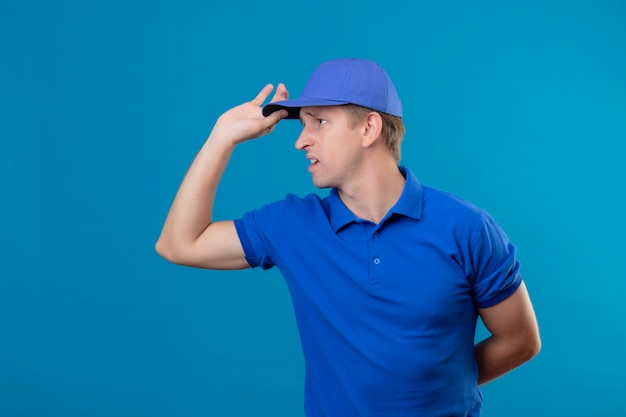 Young handsome delivery man in blue uniform and cap looking aside displeased and very anxious standing over blue wall