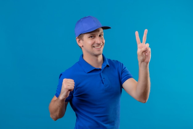 Young handsome delivery man in blue uniform and cap showing number two smiling cheerfully standing over blue wall