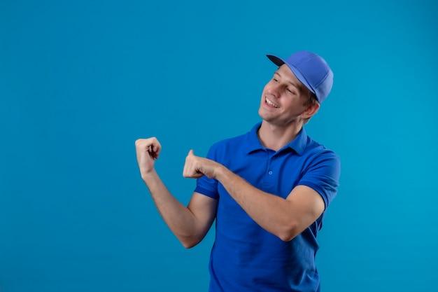Giovane uomo di consegna bello in uniforme blu e cappuccio che sorride allegramente che indica indietro con i pollici che stanno sopra la parete blu