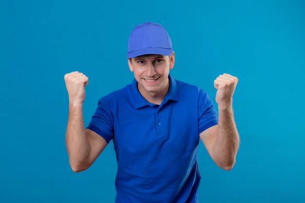 青い制服を着た若いハンサムな配達人と幸せな拳を食いしばってキャップと青い壁の上に立って彼の成功を喜んで終了