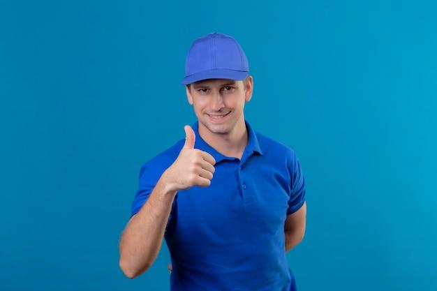 Молодой красивый курьер в синей униформе и кепке, счастливый и позитивный, улыбающийся, дружелюбный, показывает палец вверх, стоя над синей стеной