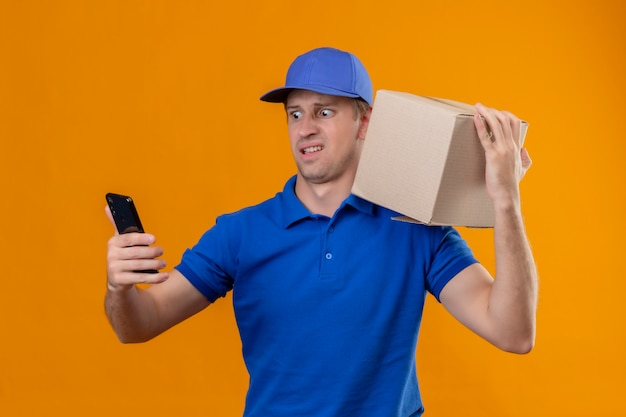青い制服を着た若いハンサムな配達人と肩にボックスパッケージを保持しているキャップ