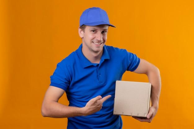 青い制服を着た若いハンサムな配達人とそれを指で指しているボックスパッケージを保持しているキャップ