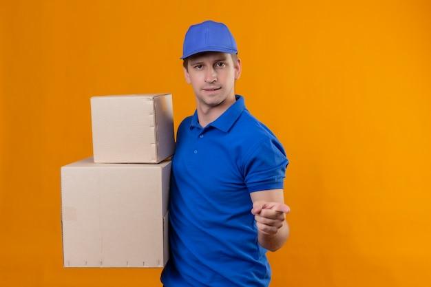 Молодой красивый курьер в синей форме и кепке держит картонные коробки, указывая пальцем на камеру, улыбаясь, стоя над оранжевой стеной