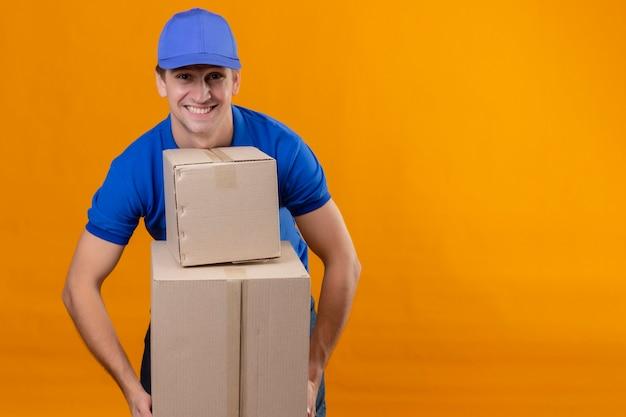Молодой красивый курьер в синей форме и кепке держит картонные коробки, весело улыбаясь и позитивно улыбаясь, стоя над оранжевой стеной