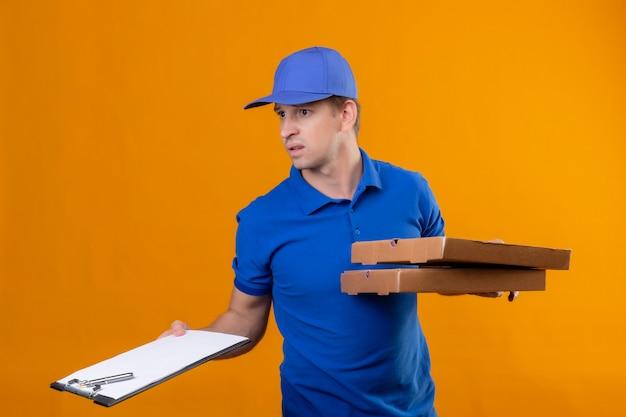Молодой красивый курьер в синей форме и кепке с коробками для пиццы и буфером обмена выглядит смущенным и очень встревоженным, стоя у оранжевой стены