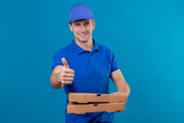 Молодой красивый курьер в синей форме и кепке, держащий коробки для пиццы, выглядит уверенно улыбаясь, показывает палец вверх, стоя над синей стеной