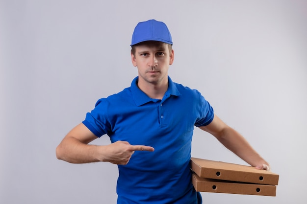 Молодой красавец-доставщик в синей форме и кепке держит коробки с пиццей, указывая пальцем на них, выглядит уверенно, стоя над белой стеной