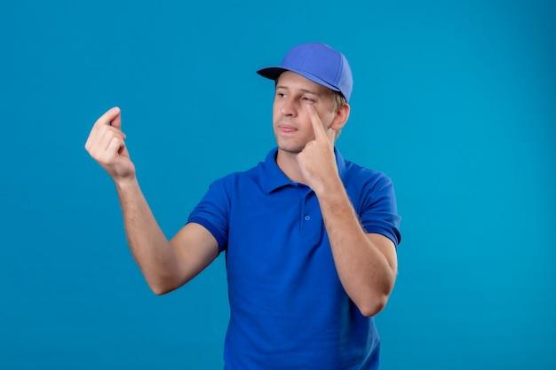Молодой красивый курьер в синей форме и кепке смотрит в сторону, указывая на его глаз, делая денежный жест в ожидании оплаты, стоя у синей стены