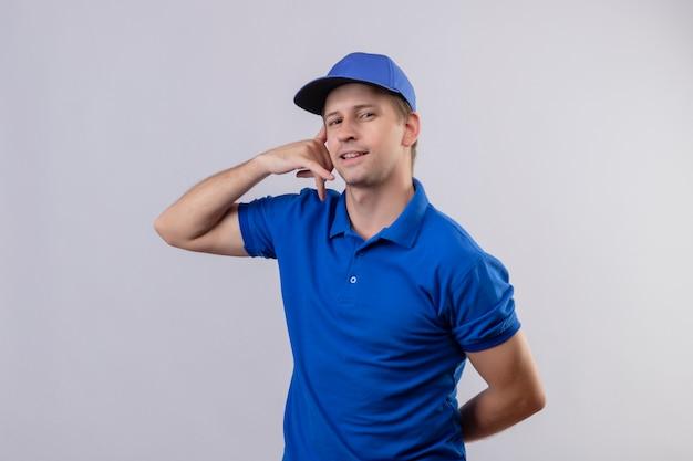 青い制服を着た若いハンサムな配達人と自信を持って笑みを浮かべて見ているキャップは私に白い壁に立っているジェスチャーを呼び出す