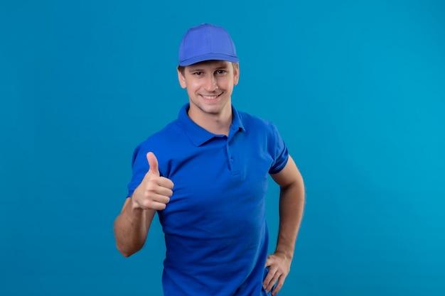Молодой красивый курьер в синей форме и кепке выглядит уверенно улыбающимся, дружелюбно показывая большие пальцы вверх, стоя над синей стеной