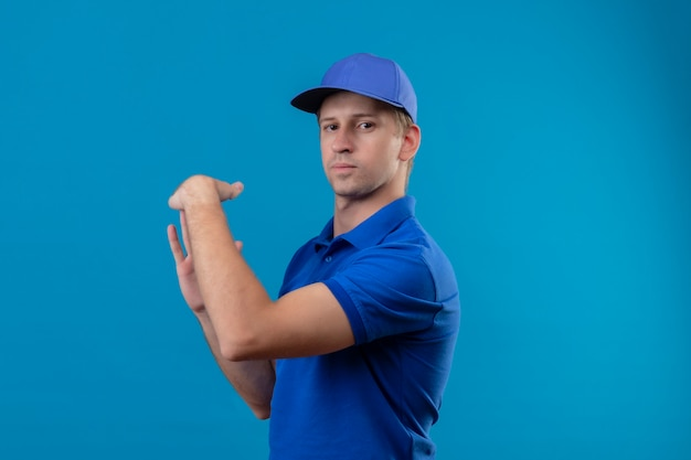 Молодой красивый курьер в синей форме и кепке делает тайм-аут руками с серьезным лицом, стоящим над синей стеной