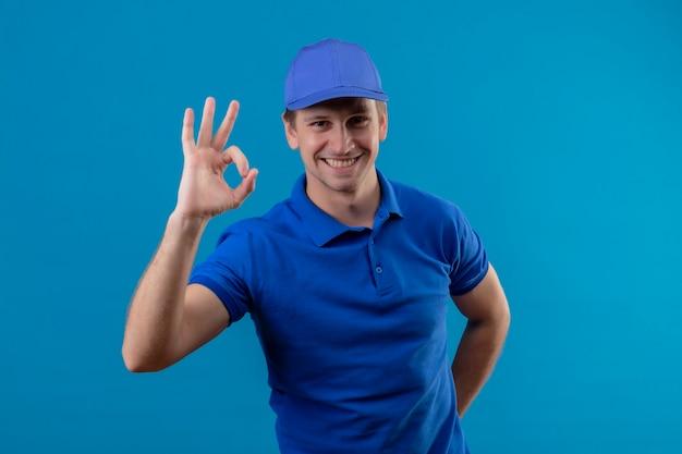 Молодой красивый курьер в синей форме и кепке, весело улыбаясь, делает знак ок, стоящий над синей стеной