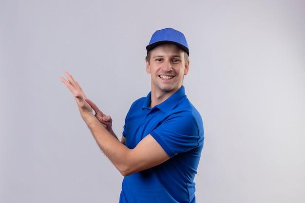 Молодой красивый курьер в синей форме и кепке дружелюбно улыбается, указывая пальцем на руку своей руки, стоящей над белой стеной