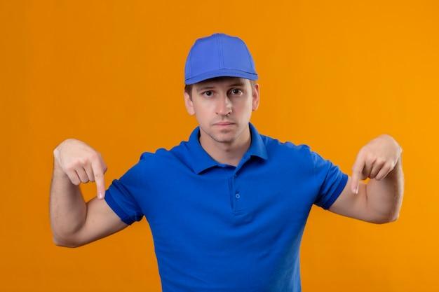 Молодой красивый курьер в синей форме и кепке с серьезным лицом, указывающим пальцами вниз, стоя над оранжевой стеной