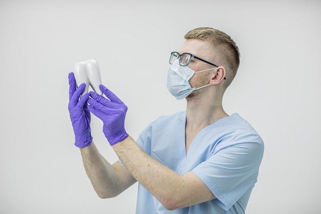 Молодой красивый стоматолог в очках и защитной маске держит модель коренного зуба