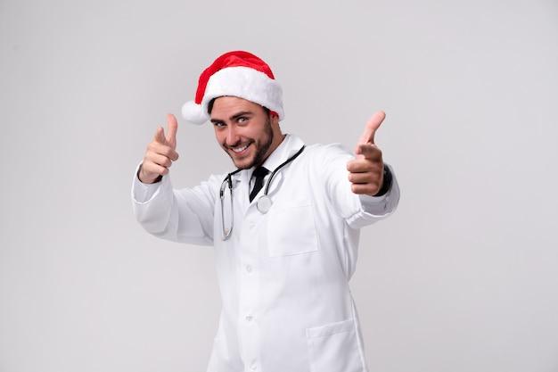 白い制服とサンタクロースの帽子の若いハンサムな医者