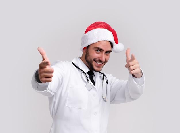 白い制服とサンタクロースの帽子で若いハンサムな医者