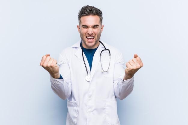 Молодой красивый доктор человек аплодисменты беззаботный и взволнованный.