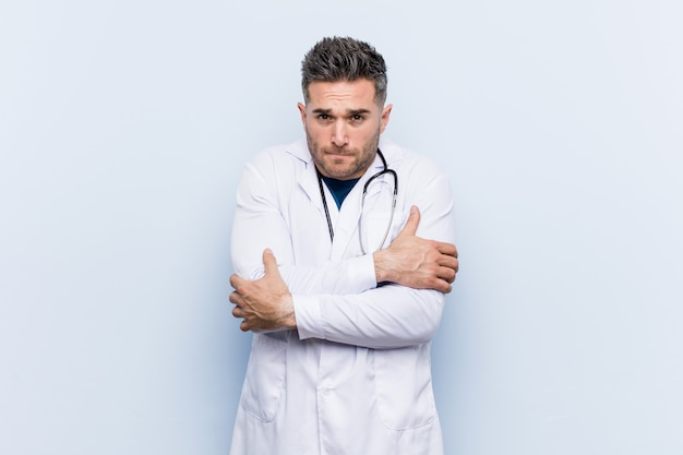 Young handsome doctor man going cold due to low temperature or a sickness