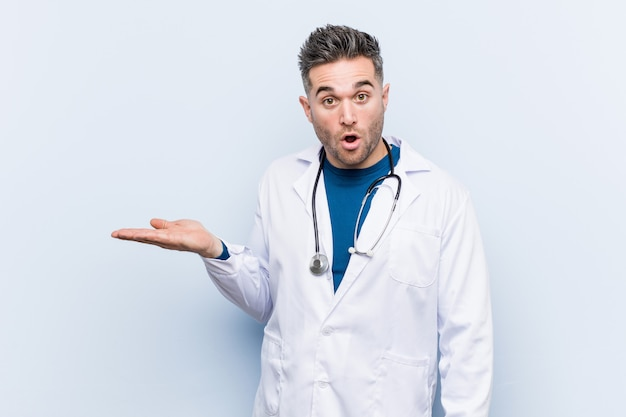 Young handsome doctor man impressed holding copy space on palm.