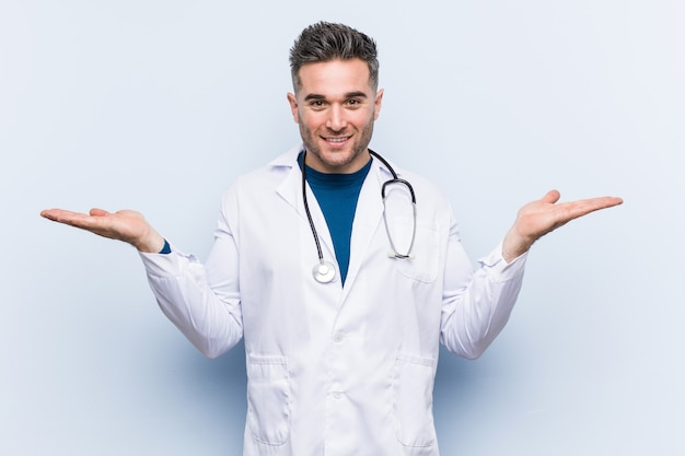 Young handsome doctor man makes scale with arms, feels happy and confident.