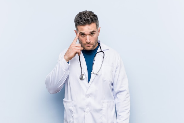 Young handsome doctor man pointing temple with finger, thinking, focused on a task.