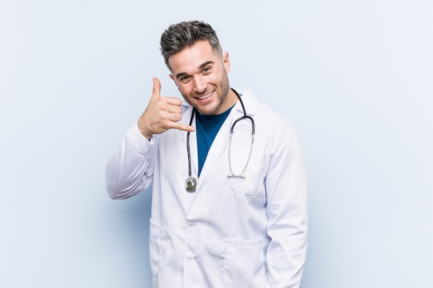 Young handsome doctor man showing a mobile phone call gesture with fingers.